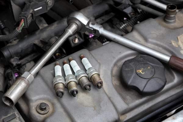 свечной ключ и 4 свечи лежат на двигателе